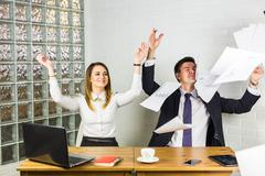 Business people excited happy smile, throw papers, documents fly in air, success Stock Photos