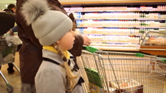 Little girl looking at shop window in a big crowded supermarket Stock Footage