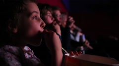 Little girl watching a movie and eating popcorn at the movie theater Stock Footage