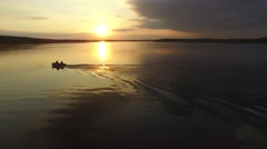 A small rubber boat moving quickly on the river at sunset. Aerial view. Stock Footage