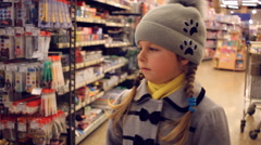 Little girl is waiting among the windows with stationery in a supermarket Stock Footage