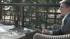 Beautiful young groom holds glass of champagne sitting on the veranda of summer Stock Footage