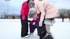 The woman and a four children skating together at ice rink Stock Footage