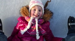 Little girl lying on the ice and pushes human legs using hands Stock Footage