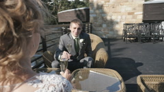Bride and groom holding glasses of champagne sitting on the veranda of summer Stock Footage