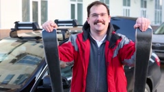 Smiling man is leaning on ski next to the car on the street Stock Footage