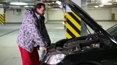 A man looking under hood and pulls out dipstick to check the oil level Stock Footage