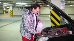 A man pours a liquid in a tank under the hood of a car Stock Footage