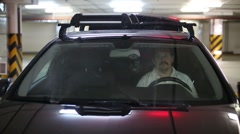 The driver washes the windshield of the car at indoor parking Arkistovideo