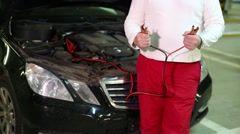The man with the terminals and wires in his hands standing at the car Stock Footage