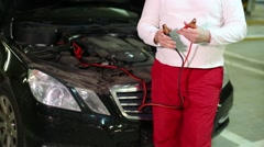 A man disconnects the wires from the battery in the car Stock Footage