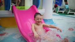 The boy slides on children slide at the indoor water park Stock Footage