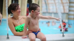 A woman and her son playing with a jet of water in the aquapark Stock Footage