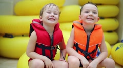 Two boys in life jackets jump on a big inflatable ring in the aquapark Stock Footage