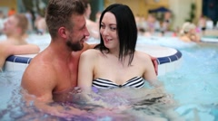 A man and a woman are sitting in a pool of a seething water Stock Footage
