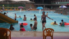 Chinese children swim in the swimming pool with their parents Stock Footage
