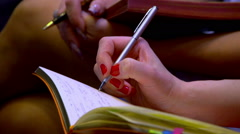 Female hand writing on a piece of paper Stock Footage