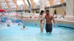 The couple is embracing at a shallow pool in the aquapark Stock Footage