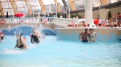 Crowded water park, a young couple running in the pool Stock Footage
