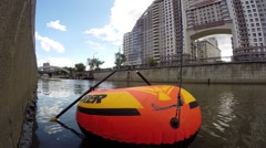 Orange inflatable boat with paddles is moored on city river Stock Footage