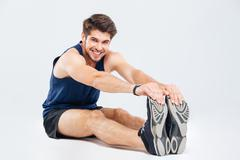 Happy handsome young man athlete sitting and stretching - stock photo