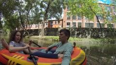 Man and woman sail in inflatable boat in city River at summer Stock Footage