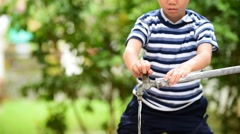 Young Thai boy take water from old faucet in the garden to drink. Stock Footage