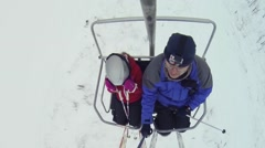 Man with girl makes selfie on cableway in ski resort, top view Stock Footage