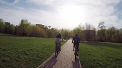 Riding bicycle in green park with bridge in Moscow, FPV Stock Footage