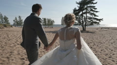 Couple holding hands running on the beach, moving the camera around Stock Footage