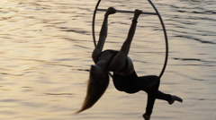Silhouette of air gymnastics woman relaxed above the water - stock footage