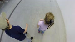 Girl and boy roller skate in underground parking, top view Stock Footage
