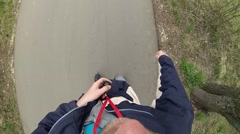 Roller skater man rides on asphalt path in park, selfie, top view Stock Footage