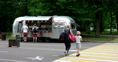 People buy food from a silver food truck Stock Footage