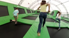Boy, woman, girl run and jump on trampoline in park Sokolniki Stock Footage