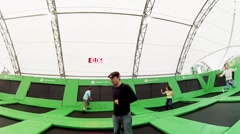 Man, boy, woman, girl jump on trampoline in park Sokolniki. Stock Footage