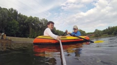 Man makes selfie and boy rowing on inflatable boat on pond Arkistovideo