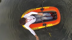 Man holds selfie stick and paddled on inflatable boat, top view Stock Footage