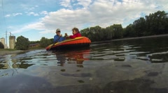 Happy brother and sister sail on inflatable boat on pond at summer Stock Footage
