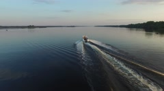 A small motorboat quickly glides over the surface of the river. Aerial view. Stock Footage