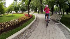 Girl in helmet rides bicycle in summer garden, back view Stock Footage