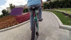 Boy teenager and girl in helmet ride bicycle in summer garden Stock Footage