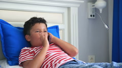 Child lying on a bed and talking on the phone 2 Stock Footage