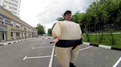 Roller skater in fat costume makes selfie and rides near woman skater and Stock Footage