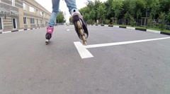 Girl roller skates near residential buildings, woman stands on grass Stock Footage
