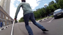 Roller skater in jeans makes selfie and rides near buildings Stock Footage