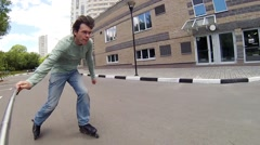 Roller skater man in jeans makes selfie and rides near buildings Stock Footage