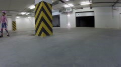 Boy and girl roller skate around column in underground parking Stock Footage