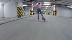 Girl in helmet roller skates in underground parking, back view Stock Footage