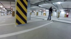 Girl in helmet and boy roller skate in underground parking Stock Footage